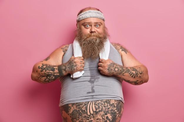 스포츠 옷을 입은 진지한 뚱뚱한 남자의 사진은 근육질 몸매에 대한 꿈을 꾸고, 몸에 열심히 일하고, 체중을 줄이고, 팔에 문신을하고, 큰 배를 가지고, 피트니스 트레이너와 함께 신체 운동을합니다.