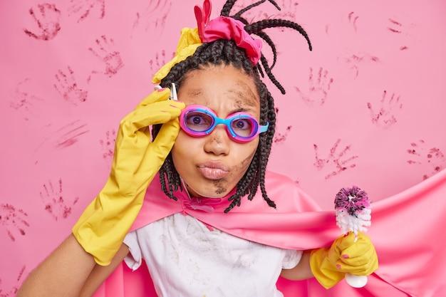 진지한 여성 가정부 슈퍼 히어로의 사진 집 청소 더러운 화장실 브러시 착용 고글 핑크 케이프와 고무 장갑은 집안일이나 집안일을하는 데 바쁜 척하는 척