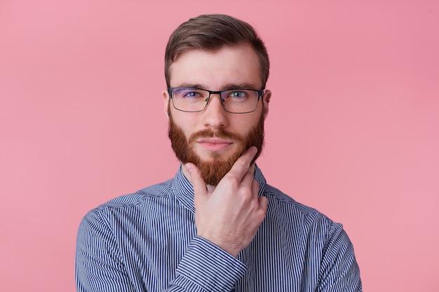 안경 스트라이프 셔츠에 심각한 젊은 매력적인 수염 난된 남자의 사진, 분홍색 배경 위에 절연 뭔가에 대해 카메라 숙고 찾고 턱 근처 손을 보유하고있다.