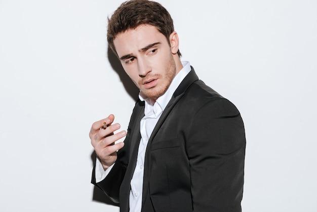 Фотография серьезного молодого бизнесмена позирует и смотрит в сторону, держа сигарету. изолированный над белой стеной.