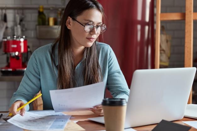 真面目な若いヨーロッパ人女性の写真は、紙の文書から情報を読み、現代のラップトップコンピューターをチェックし、キッチンのインテリアに対してポーズをとります。
