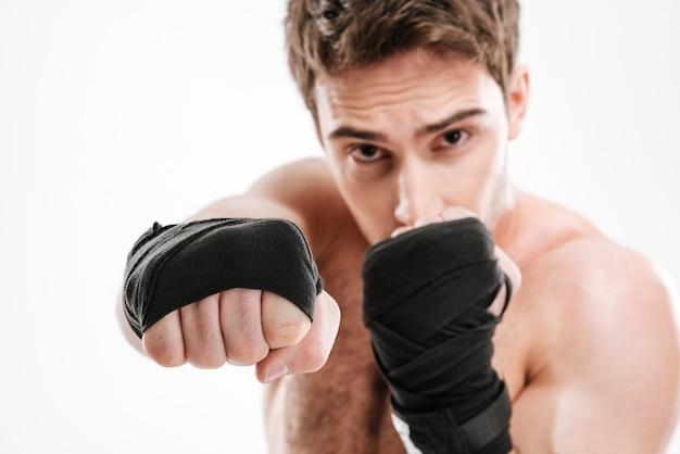 Фото серьезного боксера молодого человека делают упражнения бокса над белой стеной.