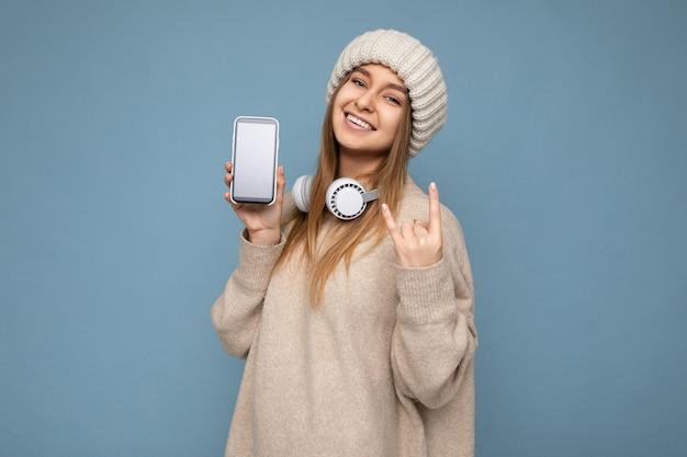 ベージュのスタイリッシュなセーターとニットベージュを身に着けているセクシーな美しいポジティブな若いブロンドの女性の写真