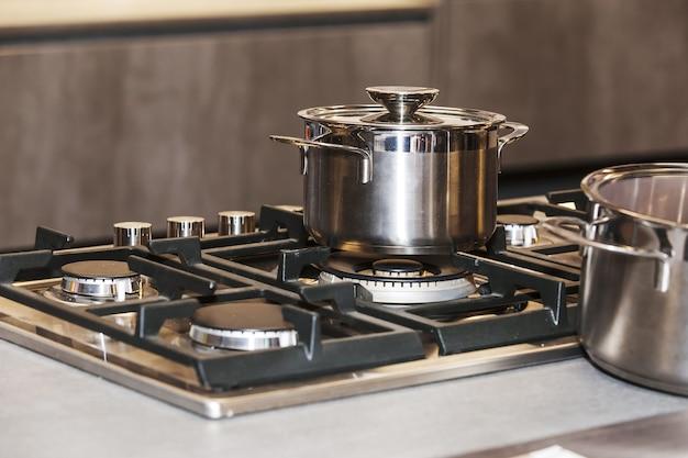 Фотография блестящей металлической сковороды на газовой плите, фокус неглубокой глубины резкости на сковороде