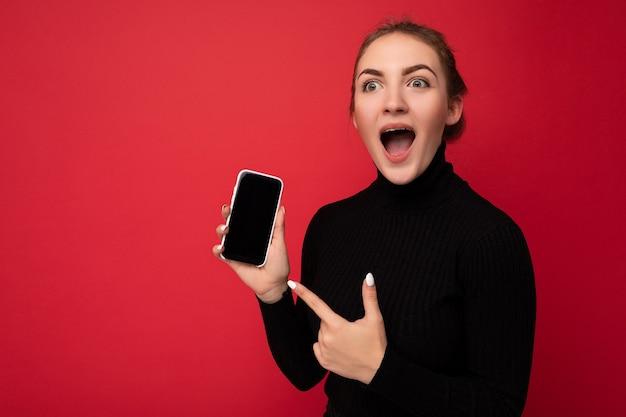 Фото шокированной привлекательной позитивной молодой брюнетки в черном свитере, стоящей изолированно