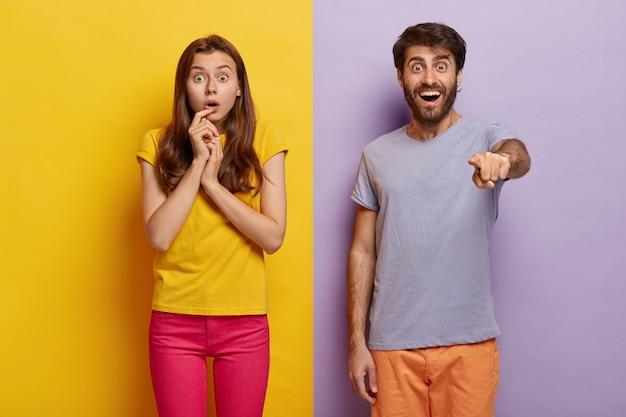 Фотография шокированной пары смотрит прямо в камеру, затаив дыхание