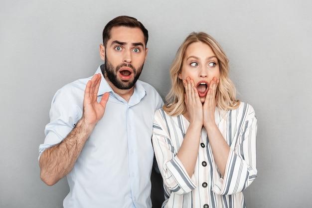 캐주얼 옷을 입고 포즈를 취하고 찾고 있는 충격된 커플의 사진