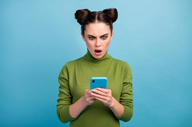 ショックを受けたクレイジーな10代の女性の写真口を開けて電話を閲覧ブログを読む否定的な投稿コメントスマートフォンユーザーは緑のタートルネックを着用します孤立した青い色の壁