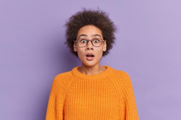 ショックを受けた巻き毛の若い女性がバグのある目を凝視し、口を開けたままにしている写真は、光学メガネのオレンジ色のニットセーターを着ている表情に驚いています。