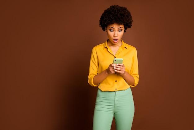 Фотография шокированной темнокожей кудрявой дамы, держащей телефон в руках, влиятельный человек с открытым ртом, читающий негативные комментарии, одетый в желтую рубашку, зеленые штаны, изолированный коричневый цвет