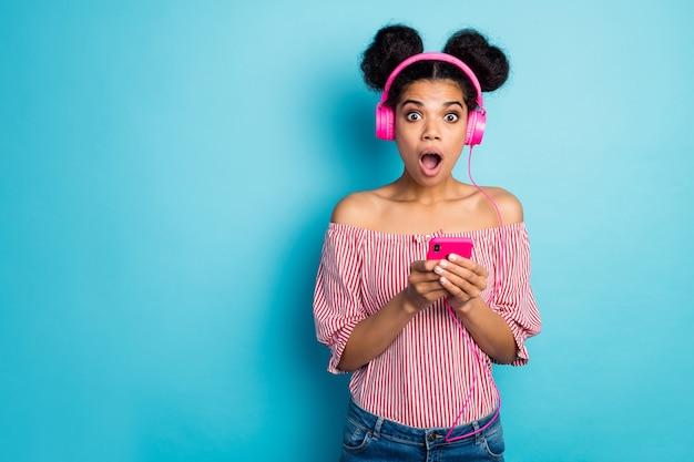 Фотография шокированной темнокожей дамы с открытым ртом подержать телефон слушать музыку наушники ужасное радио прогноз погоды носить красно-белую полосатую рубашку голые плечи изолированные стены синего цвета