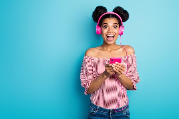 충격을받은 어두운 피부 아가씨 오픈 입을 잡고 전화 좋은 소식 읽기 음악 듣기 현대 이어폰 착용 빨간색 흰색 줄무늬 셔츠 벗은 어깨 절연 파란색 벽의 사진
