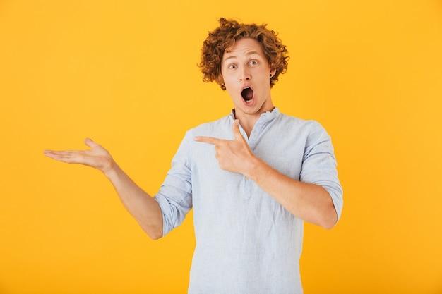 Фотография шокированного европейца, кричащего и держащего copyspace на ладони, изолированного на желтом фоне