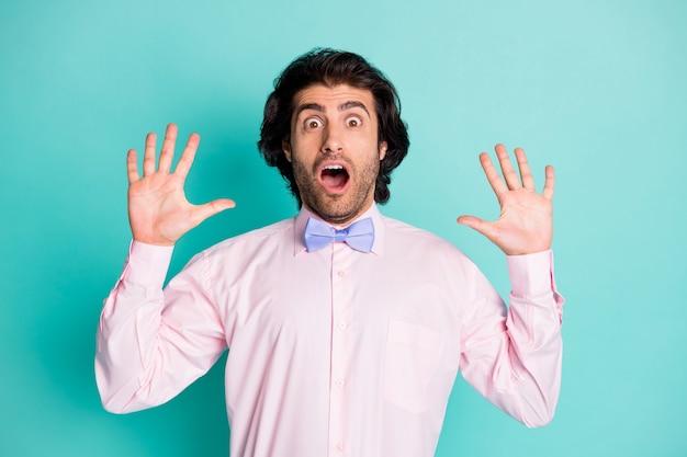 Фотография шокированного испуганного вьющихся волос мужчины, одетого в розовую рубашку двумя руками вверх, изолированный бирюзовый цвет фона