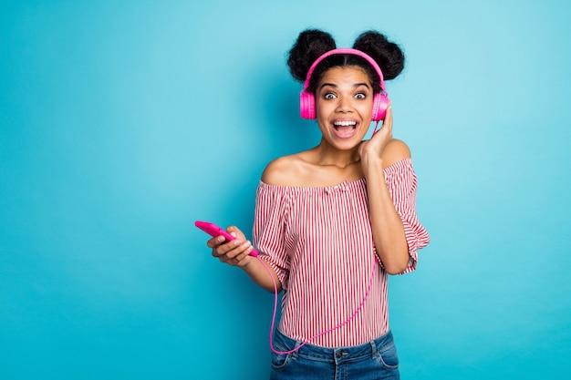 ショックを受けたファンキーなダークスキンの女性の写真は電話を保持します良いニュースを読む音楽を聞く現代のイヤホンはトレンディな赤白のストライプのシャツを着ていますオフショルダージーンズ孤立した青い色の壁