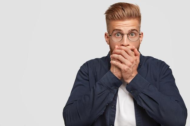 На фото шокированный рыжий мужчина с модной прической, прикрывает рот обеими ладонями, хранит интригующую информацию в секрете.