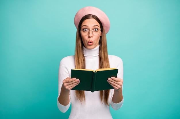 Фото потрясенной дамы держите книгу любовной истории, сюжет романа, открытый рот, неожиданный финал, окончание, технические характеристики современного розового берета, белая водолазка, изолированный, яркий бирюзовый цвет фона