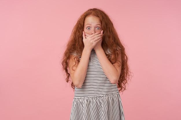 カジュアルな服装でピンクの背景の上にポーズをとって、眉を上げて、驚いてカメラを見て、手で口を覆い、目を丸くして、長い巻き毛のショックを受けた赤毛の女性の子供の写真