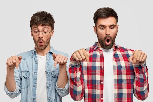 충격을받은 형태가 이루어지지 않은 두 남자의 사진은 두 손가락으로 아래를 가리키고, 턱을 떨어 뜨리고, 세련된 셔츠를 입고, 흰 벽 위에 고립 된 바닥에 이상한 것을 발견합니다. 세상에 개념