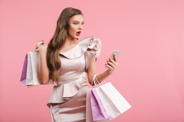 ピンクの壁に分離された買い物袋を押しながら驚きの手でスマートフォンを見てドレスを着たショックを受けた女性20代の写真