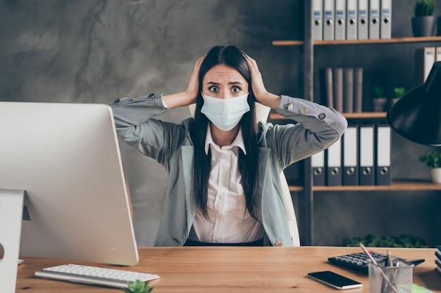 Фотография потрясенной обеспокоенной девушки, представительница агента в медицинской маске, сидит за столом, слышит босса, ужасные новости, компания обанкротилась, она потеряет работу, паника, прикоснитесь руками к голове на рабочем месте
