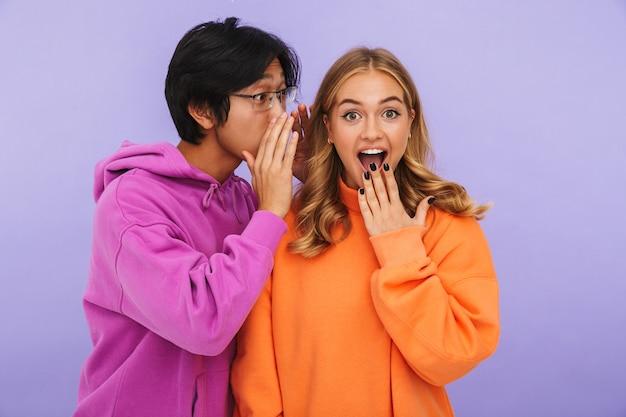 孤立してうわさ話をして立っているショックを受けた若いカップルの友人の学生の写真。