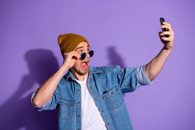 Фотография кричащего привлекательного красавца, держащего телефон с руками, делающими селфи в коричневой кепке, изолированной на ярком фиолетовом фоне