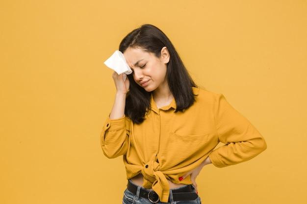 На фото больной самки болит голова. носит желтую рубашку, изолированный желтый цвет фона.