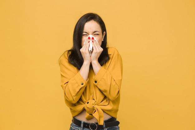 Фотография больной самки чихает. носит желтую рубашку, изолированный желтый цвет фона.
