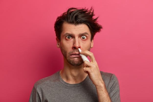 На фото больной человек страдает ринитом, заложил нос, красные глаза, распыляет лекарство от аллергии, реагирует на различные триггеры, страдает лихорадкой и простудой, пытается дышать свободно. люди, концепция болезни