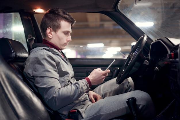 차에 앉아 손에 전화를 들고 남성 운전자의 측면 사진