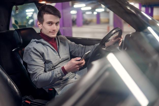 지하 보험에 차에 앉아 손에 전화를 들고 웃는 남성 운전자의 측면 사진