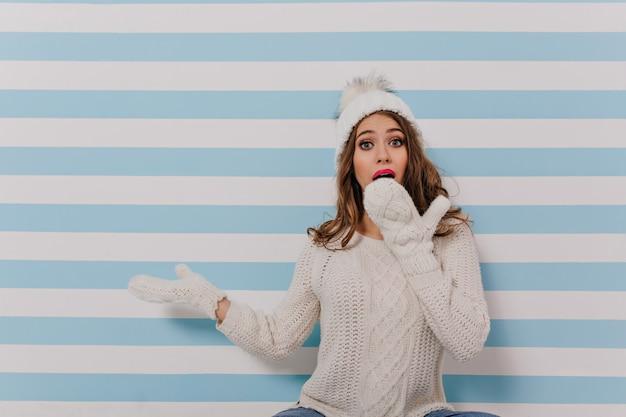 孤立した縞模様の壁に座っている女の子の写真。ニットのジャンパーを着た若い女性が手で驚いて口を閉じる