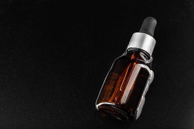 Фото бутылки сыворотки для ухода за кожей в черной волнистой воде крупным планом