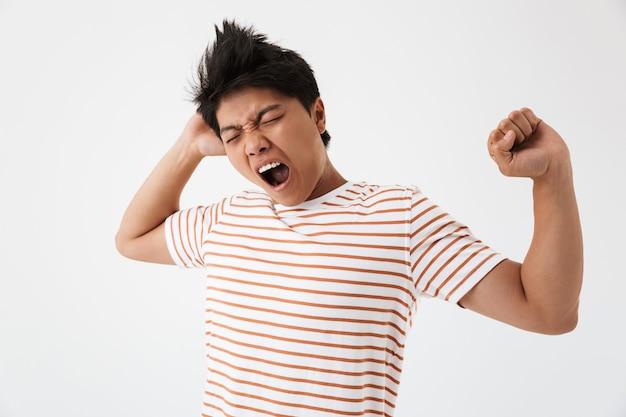 Фотография сонного азиатского мужчины с каштановыми волосами в повседневной футболке, зевающего после бессонной ночи или переутомления, изолирована