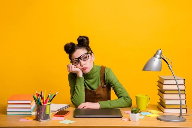 노란색 배경에 노트북이 있는 졸린 소녀 앉아 책상 사진