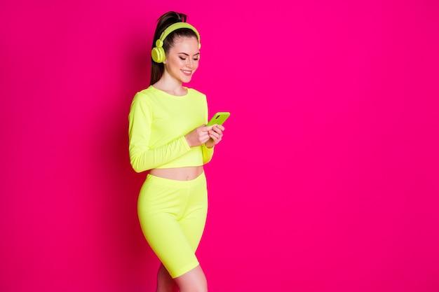 운동복을 입은 날씬한 어린 소녀의 사진은 분홍색 밝은 색 배경에 격리된 스마트폰을 사용하는 음악 헤드셋을 듣습니다.