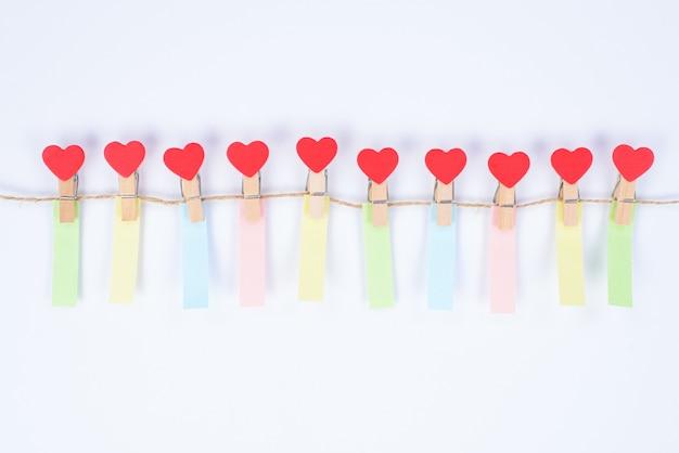 Фотография маленьких прищепок в форме сердечек, висящих на веревке, с небольшими вертикальными красочными напоминаниями, изолированными на белом фоне