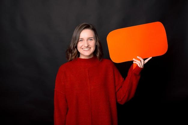 暗い背景で隔離のバブルスピーチを保持している赤いプルオーバーのスマートな女の子の写真