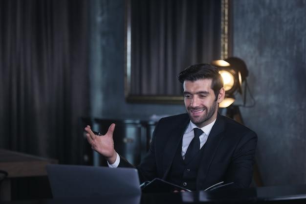 Фотография умного, умного, уверенного, милого, радостного, уверенного в себе менеджера, который проводит онлайн-конференцию через видеочат, сидя в домашнем офисе