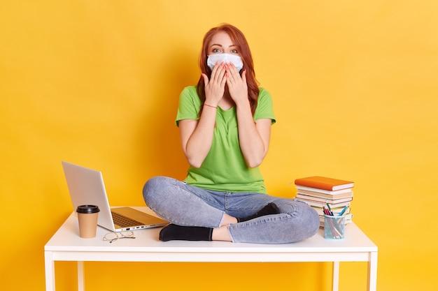 Фотография умной умной девушки сидит на столе