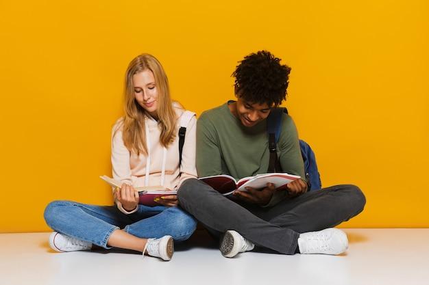 黄色の背景の上に分離された、足を組んで床に座って本を読んで使用している賢い学生16-18の写真