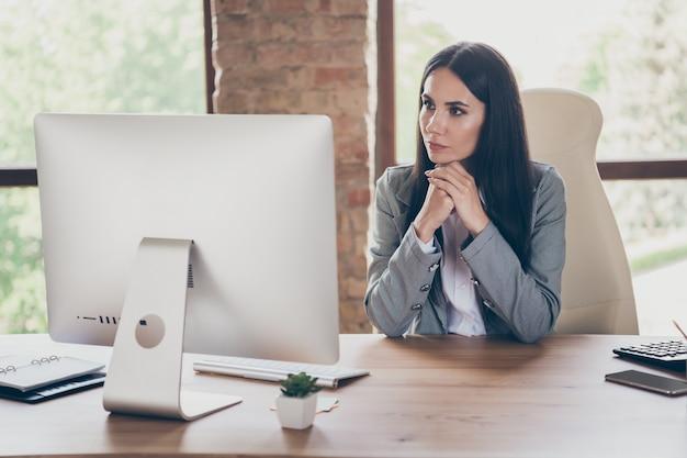 スマートな成功の写真物思いにふける女の子のエグゼクティブマーケターは、職場のワークステーションで会社開発ワークショップセミナーを聞くオンラインパートナーのためのリモート使用コンピューターを動作します