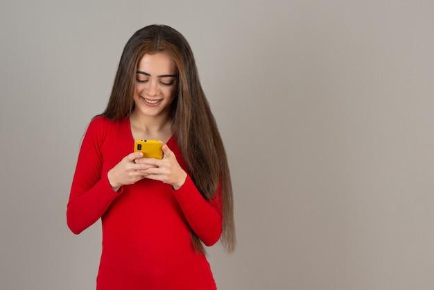 灰色の壁に携帯電話を保持している赤いスウェットシャツの笑顔の愛らしい女の子の写真。