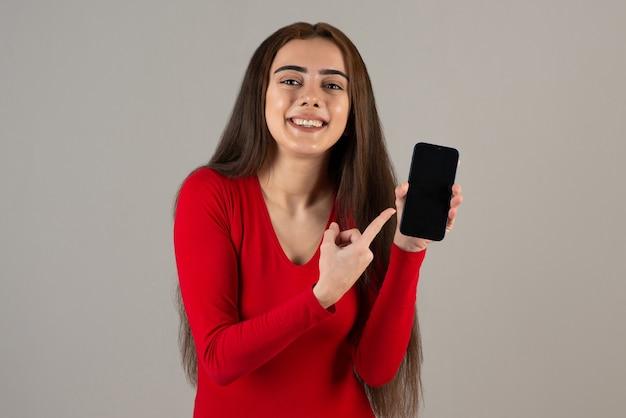 Фотография улыбающейся очаровательной девушки в красной толстовке, держащей мобильный телефон на серой стене.