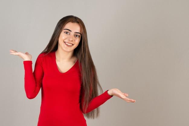 Фотография улыбающейся очаровательной девушки в красной толстовке, стоящей на серой стене.