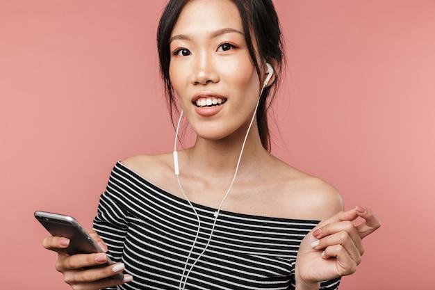 스마트폰을 들고 빨간 벽에 격리된 이어폰으로 음악을 들으며 기본적인 옷을 입고 웃고 있는 아시아 여성의 사진