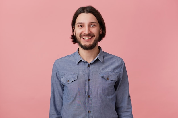 ピンクの背景の上に分離されたカメラを見て、デニムシャツの長い櫛の黒髪の笑顔のひげを生やした若い男の写真。