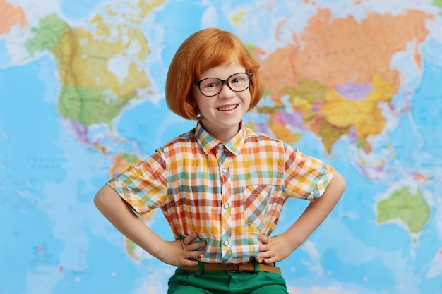 生姜髪の少年の笑顔、眼鏡をかけている、腰に手をつないでいる、地図に立ち向かいながら喜びを持っている写真