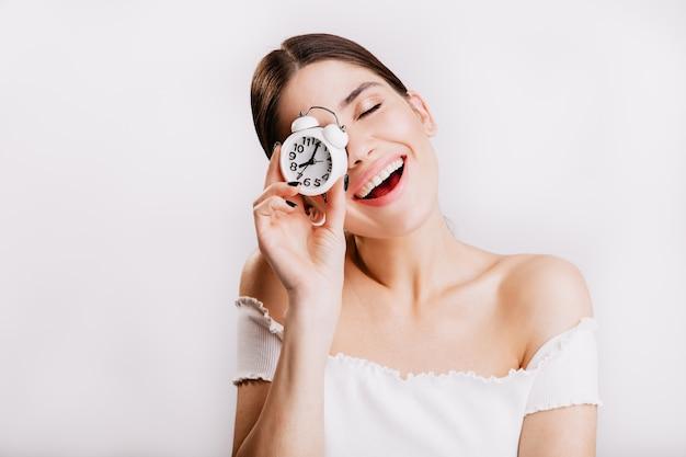 白い壁に時計でポーズをとって化粧なしでブルネットの笑顔の写真。